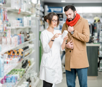 man and pharmacist looking at medicine box